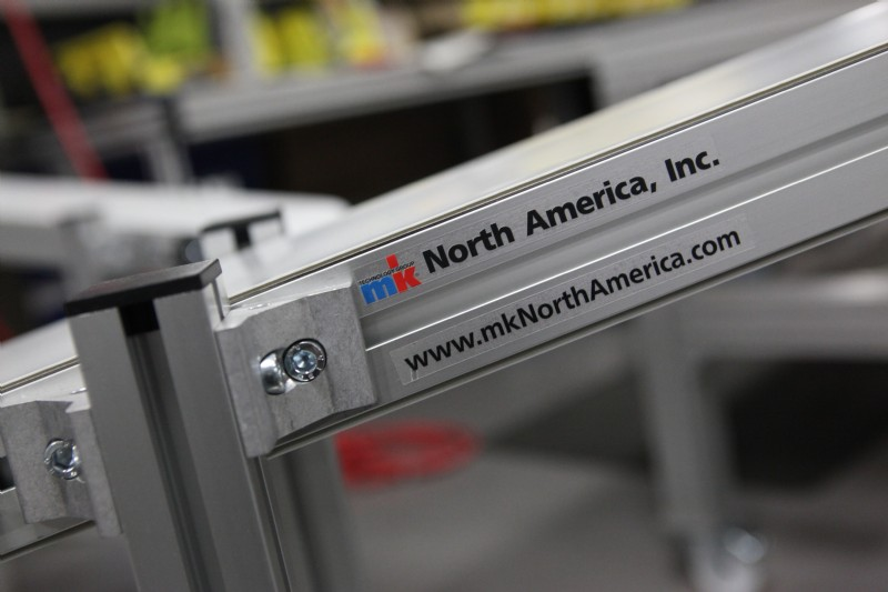 Aluminum frame conveyor with the mk North America logo