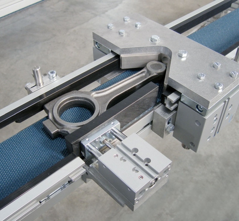Flat belt conveyor with nest and pneumatic stop