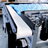 Two conveyors transferring plastic parts 90-degrees
