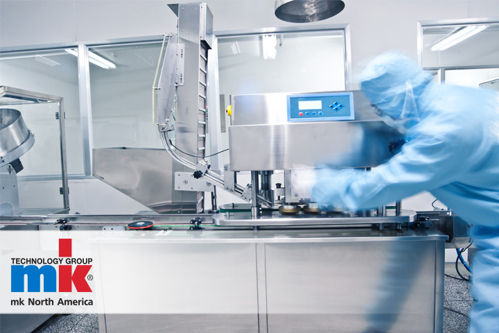 A worker using an mk conveyor system in a sterile cleanroom environment.