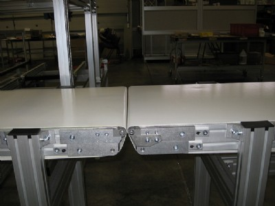 Two flat belt conveyors with rolling nose bars.