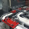 Red pallets on a flexible chain conveyor